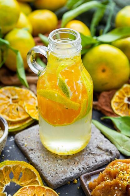 Primo piano di acqua di mandarino in una bottiglia su un tavolo con agrumi secchi e foglie Foto Gratuite