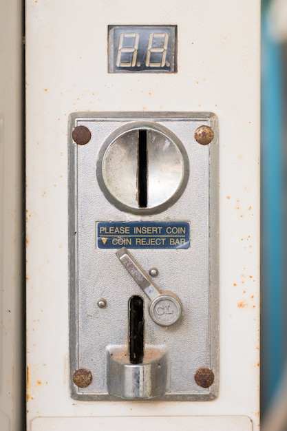 Closeup of a metal coin slot coin from a coin operated machine with an entry and exit slots Premium Photo