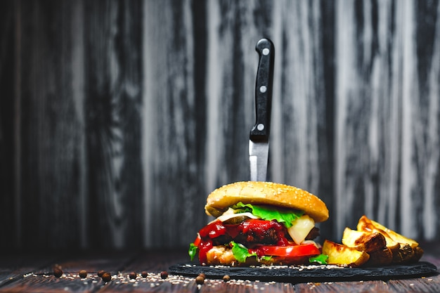 Closeup of mouth-watering, delicious homemade burgers with a knife stuck on stone board. dark Premium Photo