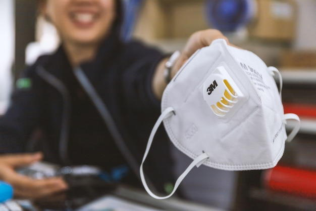 Closeup n95 air filter mask. personal protective equipment on the hands of women Premium Photo