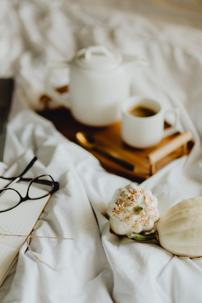 Closeup of a notebook, a cup of coffee, and white squashes in bed Premium Photo