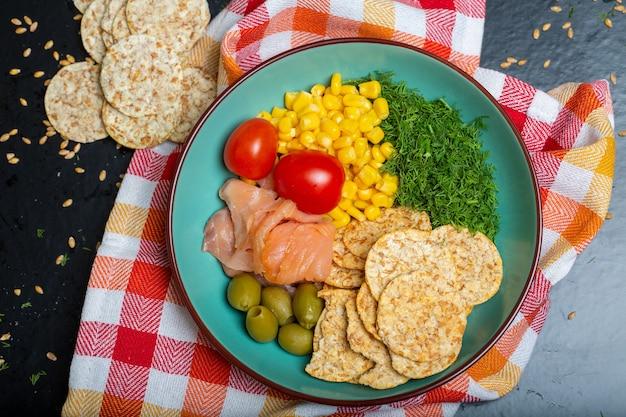 테이블에 냅킨에 연어, 크래커, 야채와 샐러드 그릇의 근접 촬영 무료 사진
