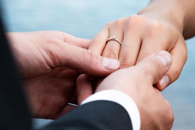 Крупным планом жених надевает кольцо на палец невесты под огнями Бесплатные Фотографии