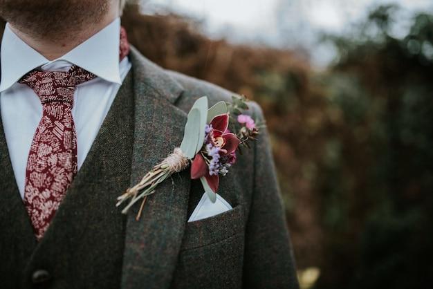 Крупным планом костюм жениха с цветами и красный узорчатый галстук с деревьями на заднем плане Бесплатные Фотографии