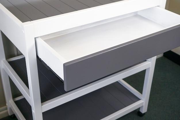 ライトの下に引き出し付きのモダンな白いテーブルのクローズアップ 無料写真