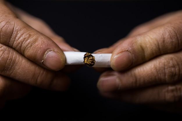Крупным планом человека, ломающего сигарету пополам - концепция отказа от вредных привычек Бесплатные Фотографии