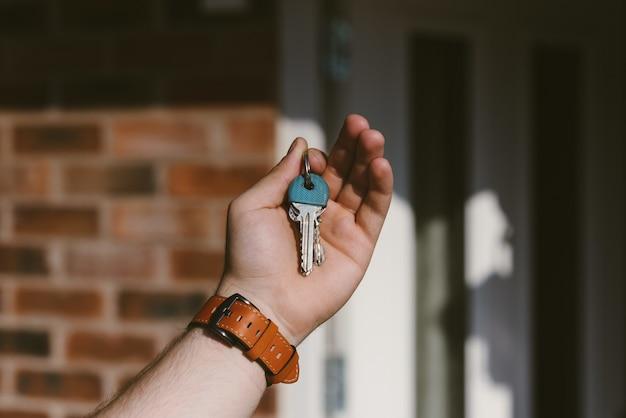 Крупным планом лицо руки, держащей ключи с размытым фоном Бесплатные Фотографии