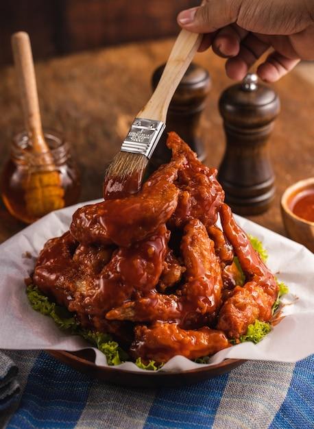 테이블에 그릇에 맛있게 요리 닭 날개에 소스를 넣는 사람의 근접 촬영 무료 사진