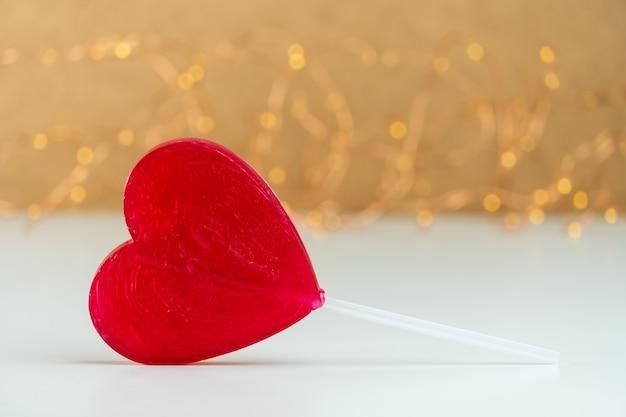 Крупным планом леденец на палочке в форме красного сердца с размытым фоном Premium Фотографии