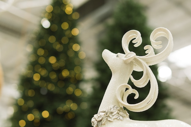 Closeup Of A Reindeer With Blurred Christmas Tree In The Background Premium Photo