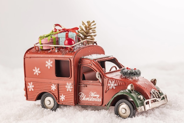 흰색 배경에 인공 눈에 그것에 크리스마스 장신구와 장난감 자동차의 근접 촬영 무료 사진