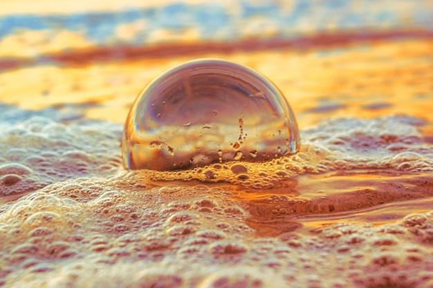 저녁 일몰 동안 바다로 둘러싸인 모래에 투명한 공의 근접 촬영 무료 사진