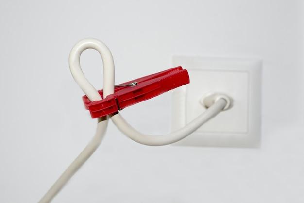 Крупным планом белый кабель и красная прищепка Бесплатные Фотографии