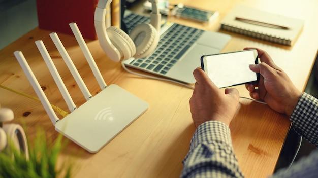 Макрофотография беспроводной маршрутизатор и человек, используя смартфон на гостиной дома в офисе Premium Фотографии