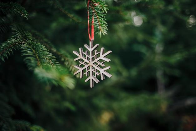 Крупным планом деревянное рождественское украшение в форме снежинки на сосне Бесплатные Фотографии