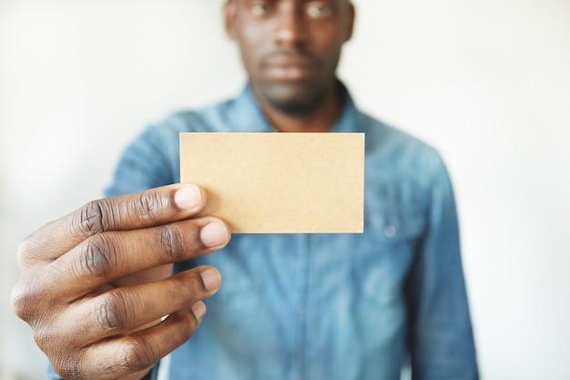 Крупным планом руки африканского человека, держа визитную карточку Бесплатные Фотографии