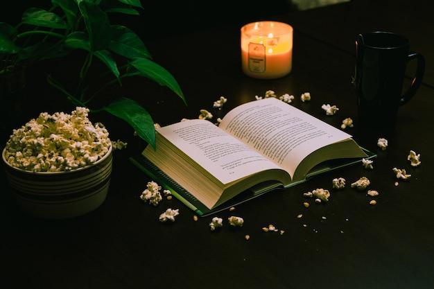 開いた本と火のともったろうそくと一杯のコーヒーとテーブルの上のポップコーンのボウルのクローズアップ 無料写真