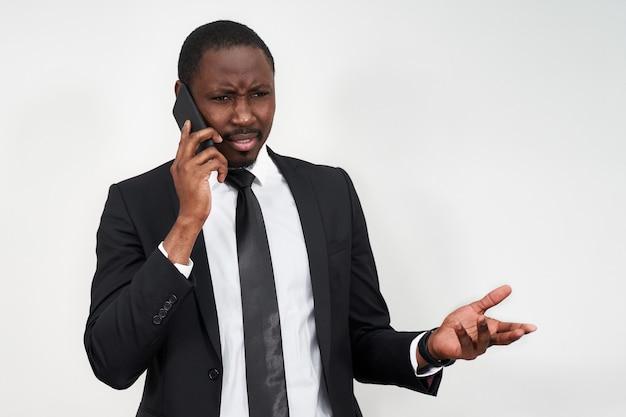 Крупный план сердитого молодого африканского человека кричащего пока говорящ на smartphone Premium Фотографии