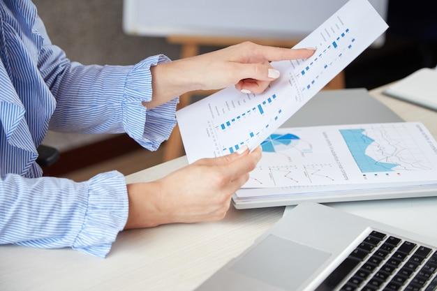 Крупный план анонимной женщины держа лист бумаги и указывая на диаграммы на ем Бесплатные Фотографии