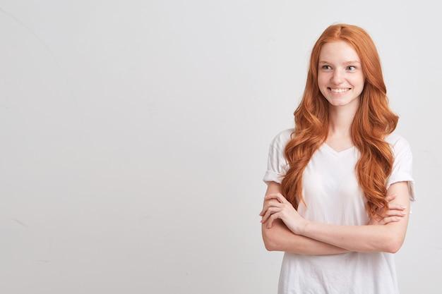 波状の長い髪とそばかすのある美しい赤毛の若い女性のクローズアップはtシャツを着て悲しみを感じ、白い壁に隔離された正面を見る 無料写真