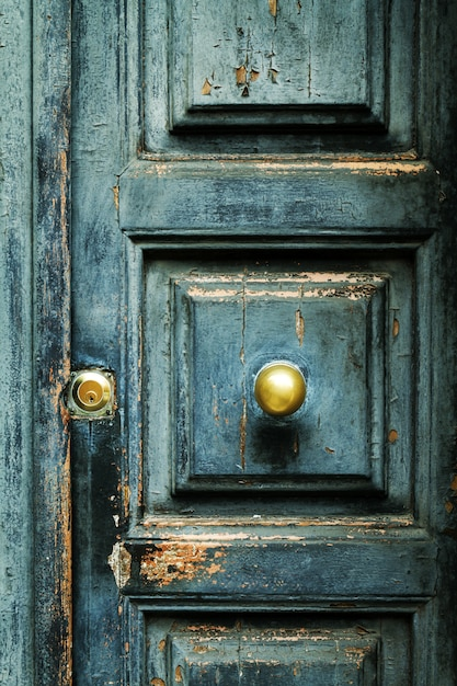Closeup of blue turquoise old textured antique door with gold br Free Photo