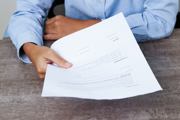 Closeup of business person giving document to viewer Free Photo