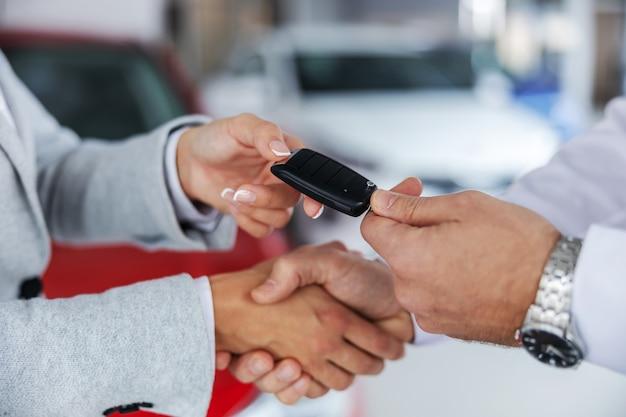車のサロンに立っている間、車の売り手と買い手が握手をしているクローズアップ。売り手は買い手に車の鍵を渡します。 Premium写真