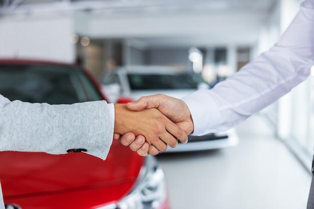 車のサロンに立っている間握手する車の売り手と買い手のクローズアップ。 Premium写真