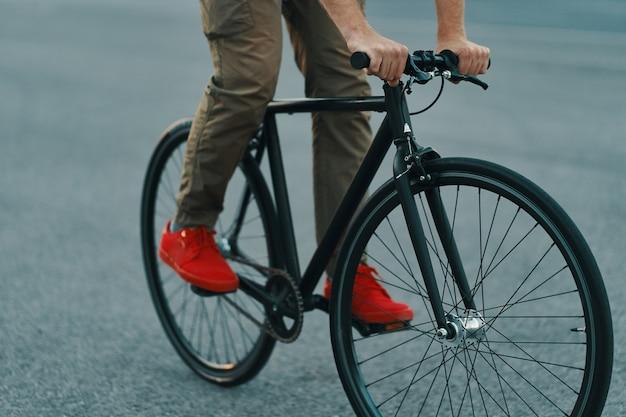 都市道路で古典的な自転車に乗ってカジュアルな男の足のクローズアップ 無料写真