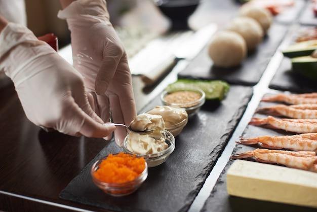 일본 음식을 준비하는 요리사 손의 근접 촬영입니다. 초밥을 만드는 일본 요리사 레스토랑에서 롤. 프리미엄 사진
