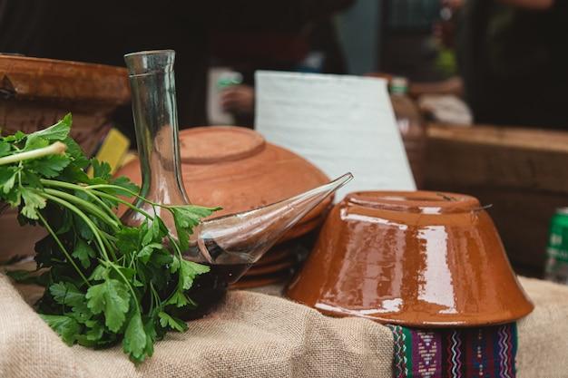 Крупным планом глиняные горшки, банки и травы на столе под огнями с размытым фоном Бесплатные Фотографии