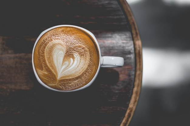 コーヒーカップの女性のクローズアップは、コーヒーショップの空撮でコーヒーを楽しむ Premium写真