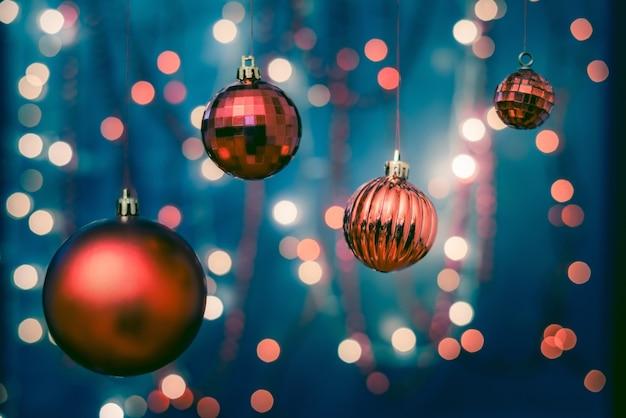 흐릿한 배경 및 Bokeh 조명과 함께 크리스마스 트리에 화려한 장신구의 근접 촬영 무료 사진