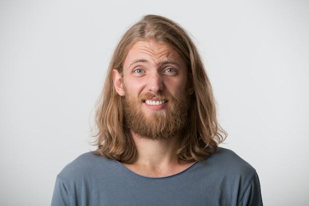 あごひげと金髪の長い髪の混乱した悲しい若い男のクローズアップは灰色のtシャツを着て恥ずかしがり屋と白い壁に孤立して動揺を感じます 無料写真