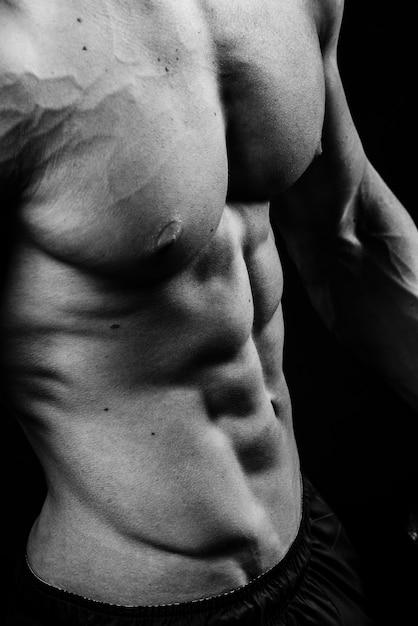 복근 가슴 6 팩 근육 가슴 흑백 스튜디오, 세로 사진과 함께 멋진 완벽한 섹시한 강한 관능적 인 벌거 벗은 몸통의 근접 촬영 프리미엄 사진