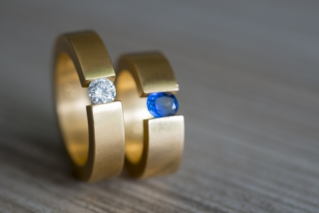 木製のテーブルにダイヤモンドとサファイアのカップルの黄金の結婚指輪のクローズアップ 無料写真