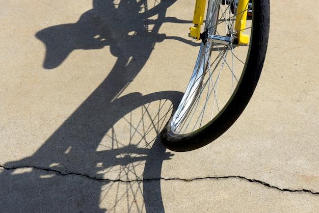 曲がった自転車の車輪のクローズアップ、歩道に超現実的な影を投影 Premium写真