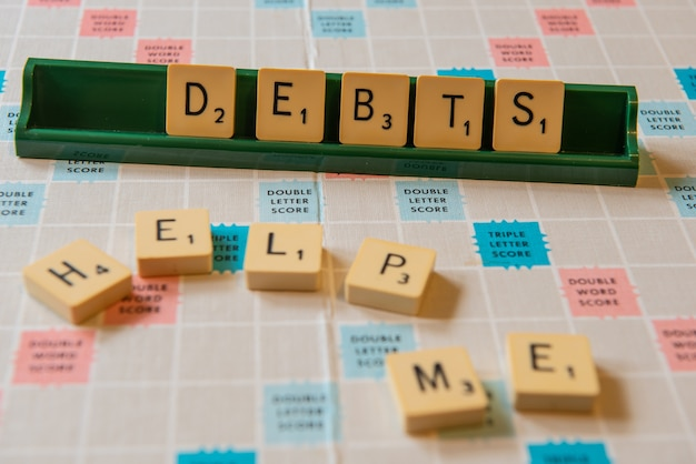 借金のクローズアップとライトの下でスクランブルボードに書くのを手伝ってください 無料写真