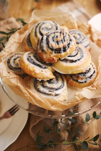 나무 테이블에 설탕 유약과 함께 맛있는 양귀비 달팽이 파이의 근접 촬영 무료 사진