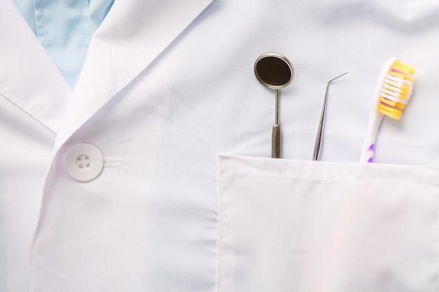 Крупный план зубоврачебного инструмента, зубной щетки и зеркала в белом кармане медицинской формы. Premium Фотографии