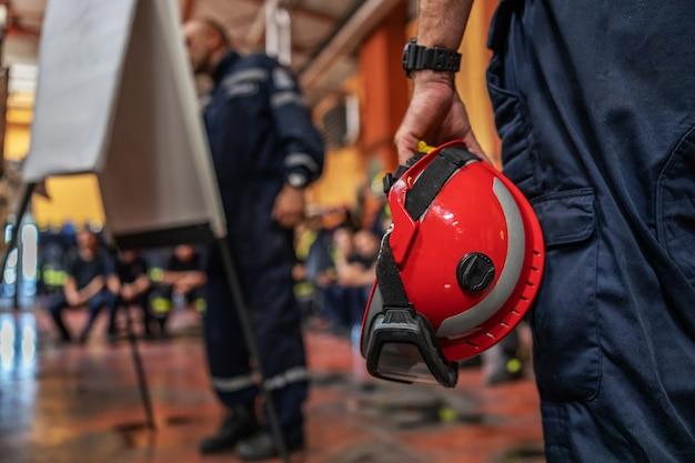 消防士がヘルメットをかぶって、事故を描いて話している上司の話を聞いているクローズアップ。 Premium写真