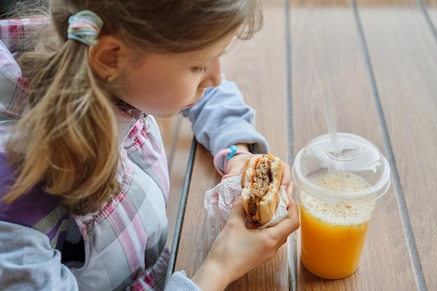 햄버거를 먹고 오렌지 주스를 마시는 아이의 손의 근접 촬영 프리미엄 사진