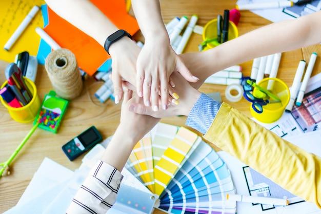 クリエイティブ・オフィスの机の上に互いの上に手を繋いでいるビジネス人々の手のクローズアップ。色見本、部屋のレイアウトのあるテーブルにいる建築家やインテリアデザイナー。チームワークの概念。 Premium写真
