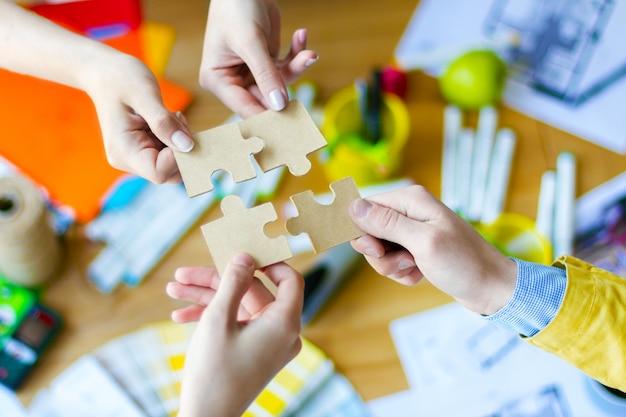 クリエイティブ・オフィスの机の上にパズルを置くビジネス人々の手のクローズアップ。色見本、部屋のレイアウト、事務用品のテーブルにいる建築家やインテリアデザイナー。チームワークの概念。 Premium写真