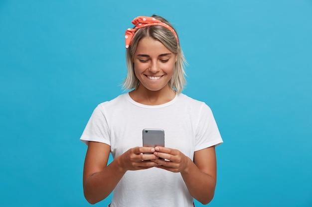 幸せな魅力的な金髪の若い女性のクローズアップは白いtシャツを着ています 無料写真