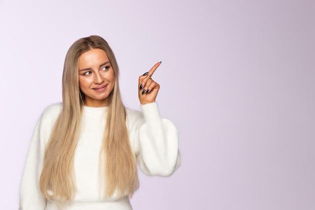 Крупный план счастливой женщины указывая и представляя палец вверх, показывая пустой космос экземпляра с ее пальцем, мягкой фиолетовой стеной. Premium Фотографии