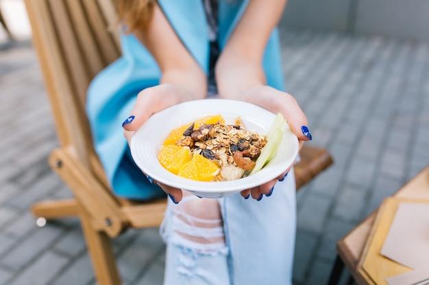 Крупным планом здоровый завтрак в руках молодой женщины, сидящей в кресле Бесплатные Фотографии