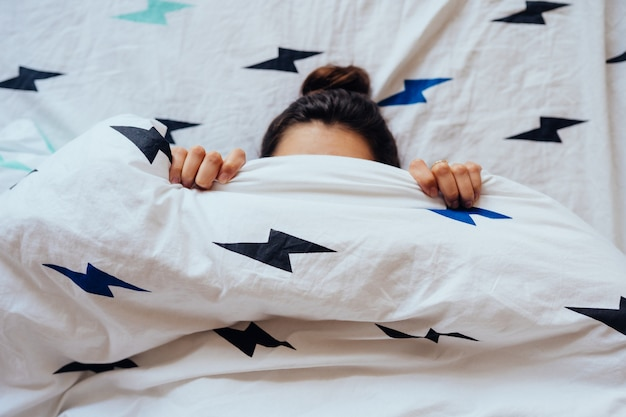 Крупный план симпатичной молодой женщины лежит в кровати покрытой с одеялом. Бесплатные Фотографии