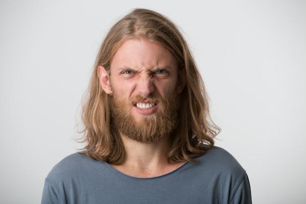 ひげと金髪の長い髪の狂った狂気の若い男のクローズアップは灰色のtシャツを着て怒っているように見え、白い壁の上に孤立して不機嫌に見える 無料写真