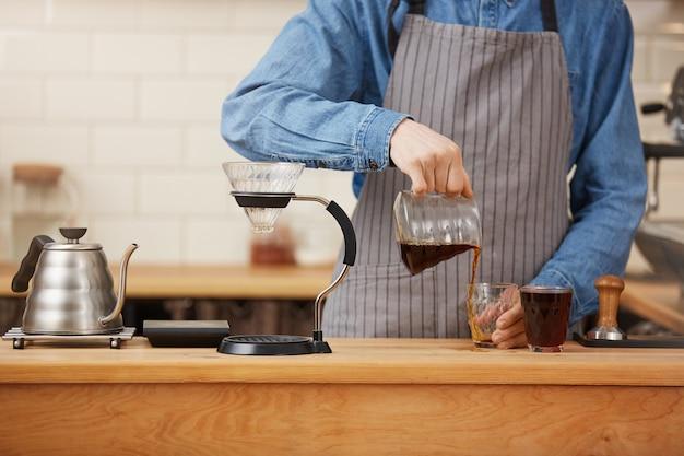 Крупный план мужского бариста вручает лить альтернативный кофе от chemex. Бесплатные Фотографии